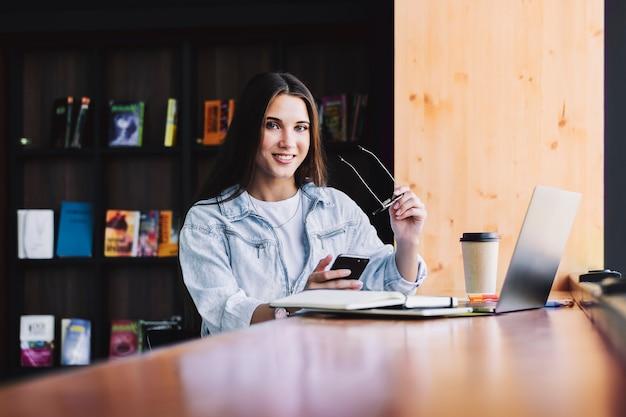 Aantrekkelijke zakenvrouw zit aan tafel voor laptop, bericht schrijft, smartphone gebruikt, gesprekken over de telefoon.