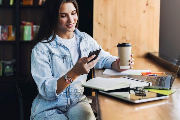 Aantrekkelijke zakenvrouw zit aan tafel voor laptop en praat over de mobiele telefoon, onderhandelt over de telefoon.