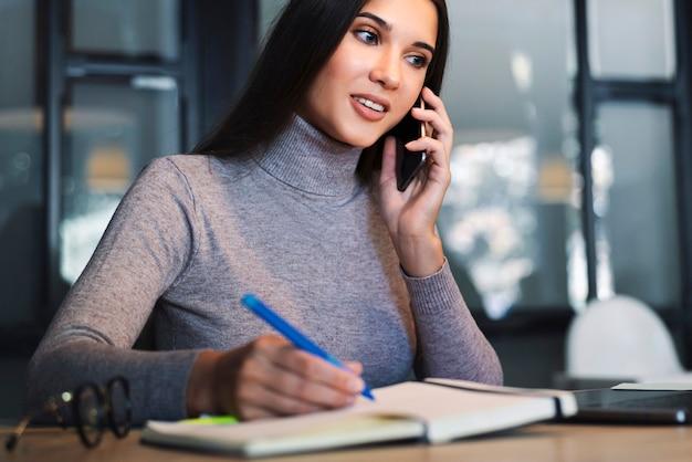 Aantrekkelijke zakenvrouw zit aan tafel voor laptop, maakt aantekeningen in notitieblok, zakelijke planning opstelt.