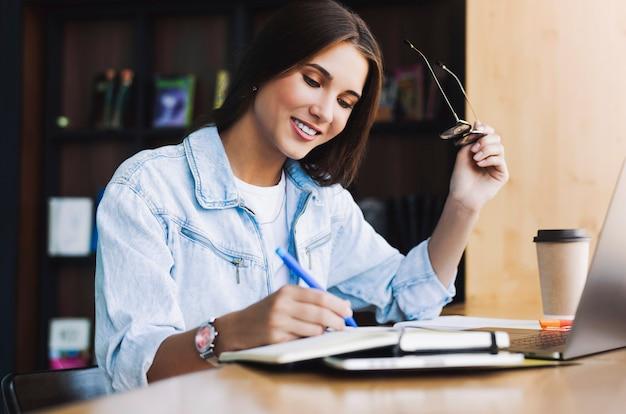 Aantrekkelijke zakenvrouw zit aan tafel voor laptop. mooie brunette meisje glimlacht, houdt een bril