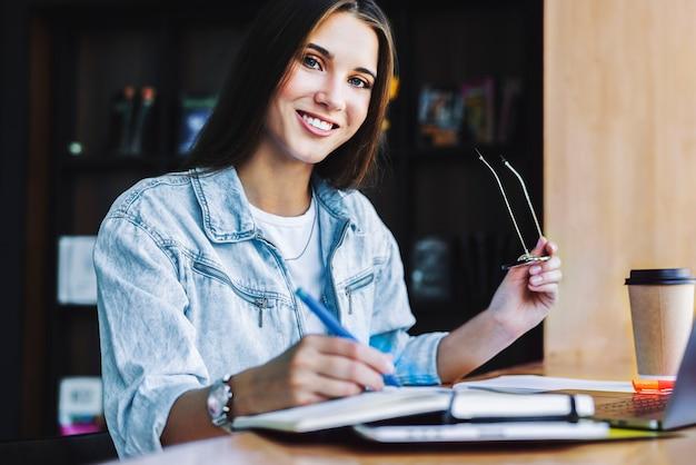 Aantrekkelijke zakenvrouw zit aan tafel voor laptop. mooie brunette vrouw glimlacht, houdt een bril