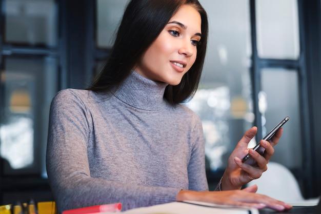 Aantrekkelijke zakenvrouw zit aan tafel voor laptop, werkt op afstand terwijl in café.