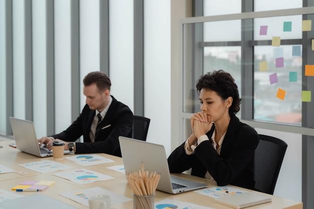 Aantrekkelijke zakenvrouw zit en denkt met serieuze uitdrukking tijdens het werken op laptop met collage aan modern bureau in kantoor. vermoeiend werk.