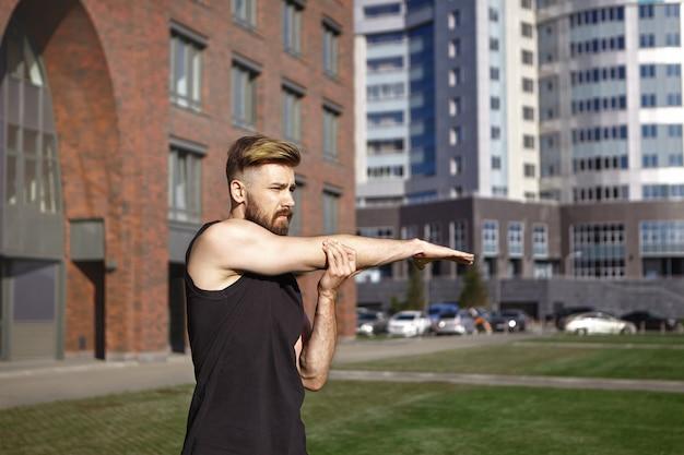 Aantrekkelijke zelfbepaalde jonge man met trendy kapsel en wazige baard die zich uitstrekt rechterarm voor cardiotraining in de ochtend, genietend van zonnig weer in een stedelijke omgeving. sport en vitaliteit