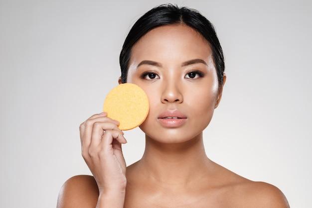 Aantrekkelijke zelfverzekerde dame die haar gezicht met wattenschijfje schoonmaakt
