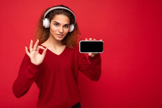 Aantrekkelijke zelfverzekerde jonge brunette krullende vrouw die een donkerrode trui draagt die op rood wordt geïsoleerd