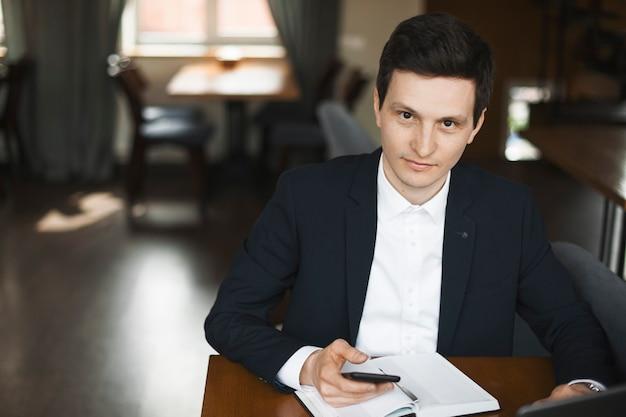 Aantrekkelijke zelfverzekerde jonge zakenman glimlachend terwijl hij een smartphone in zijn hand zittend in een restaurant.