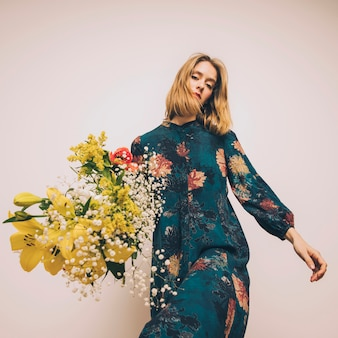 Aantrekkelijke zelfverzekerde vrouw in jurk met boeket verse bloemen