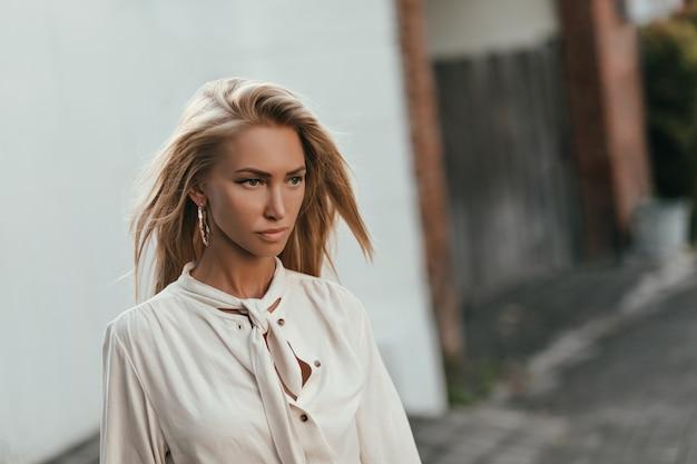 Aantrekkelijke zelfverzekerde vrouw in lichte witte blouse loopt naar buiten