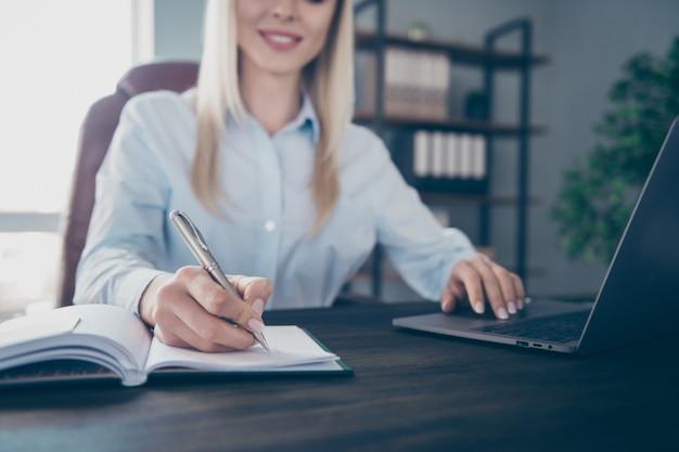 Aantrekkelijke zelfverzekerde zakenvrouw schrijft planner pc aan het typen