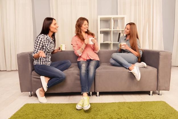 Aantrekkelijke zusters zittend op de bank en praten met koffie