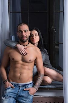 Aantrekkelijke zwangere brunette vrouw in een gebreide jurk zit op de vensterbank en knuffelen haar man met blote borst en getatoeëerde handen. laatste maanden zwangerschap.