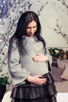 Aantrekkelijke zwangere brunette vrouw in een jurk handen houden op buik staande in de buurt van bed met bloemen op het ledikant in de slaapkamer. laatste maanden zwangerschap.