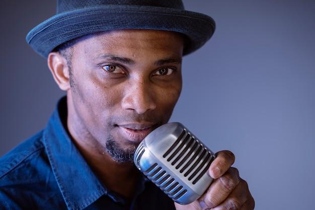 Aantrekkelijke zwarte man op het punt om een vintage lied te zingen. geïsoleerde man zingen etnische culturele liedjes. jonge afro-amerikaanse zanger die trendy microfoon. componeer en maak songteksten.