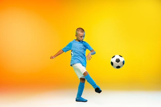 Aanval. jonge jongen als voetbal- of voetballer in sportkleding die oefent op gradiëntgeel in neonlicht