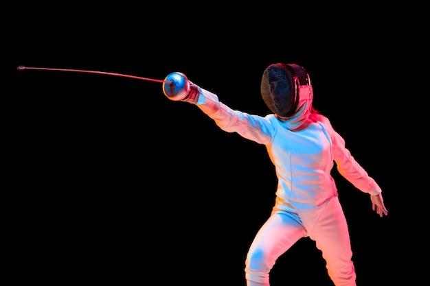 Aanvallen. tienermeisje in hekwerkkostuum met in hand zwaard geïsoleerd op zwarte muur, neonlicht. jong model oefenen en trainen in beweging, actie. copyspace. sport, jeugd, gezonde levensstijl.