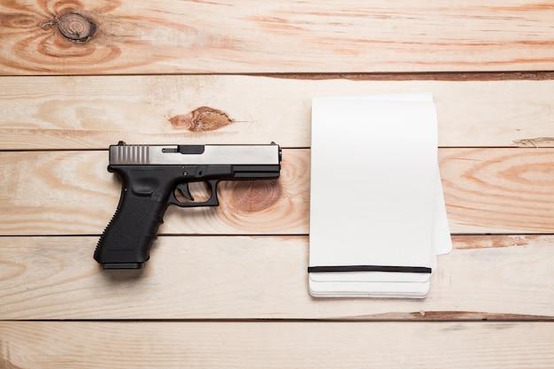 Aanvalsgeweer, pistool, mes met schede, kompas en notitieboekje met pen op tafel.