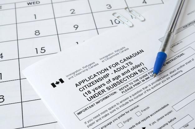 Aanvraag voor canadees staatsburgerschap voor volwassenen en blauwe pen ligt op de kalenderpagina