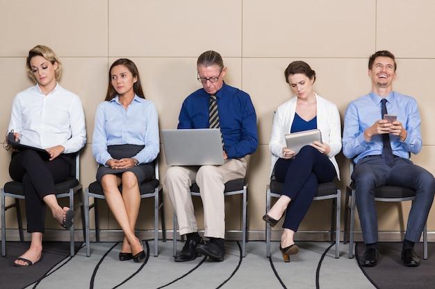Aanvragers in formele kleding zitten en wachten