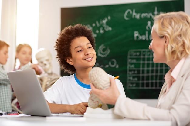 Aanvullende kennis. opgetogen positieve jongen die naar zijn leraar luisterde terwijl hij een bijles kreeg