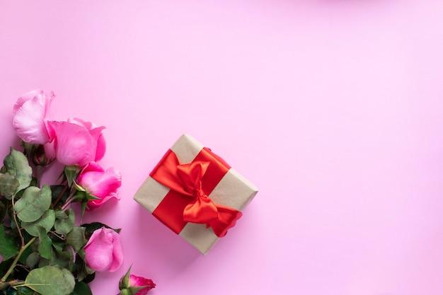 Aanwezig gebonden met rood lint en roze rozenboeket. valentijnsdag, kerstmis, moederdag, verjaardagscadeautjes. wenskaart concept