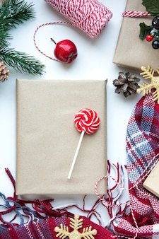 Aanwezig in bruin knutselpapier, dozen, snoep, plaid en kerstversiering op tafel. kopieer ruimte. eco-vriendelijk nieuwjaar concept