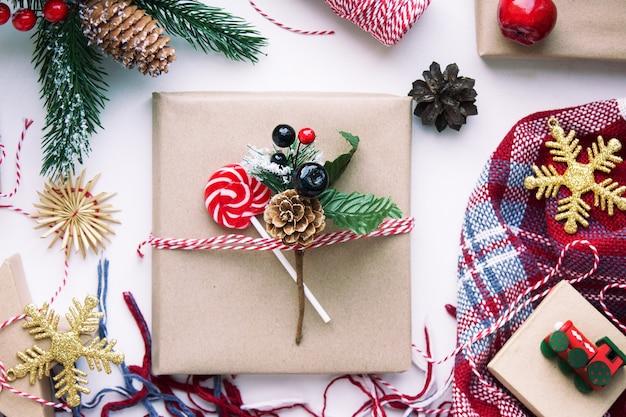 Aanwezig in bruin knutselpapier, dozen, snoep, plaid en kerstversieringen op tafel. voorbereiding op nieuwjaar