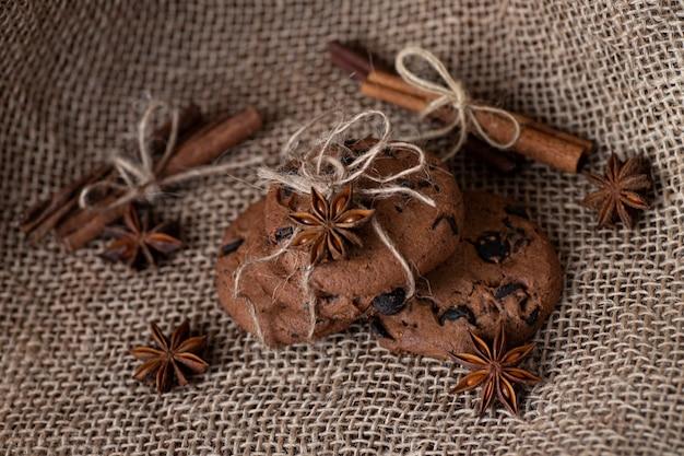 Aanwezig in de vorm van bruine koekjes met chocolade en kruiden op jute, kaneel en ster van steranijs. bakkerijproducten. snoepjes, eten