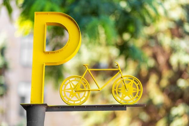 Aanwijzing van fietsenstalling. grote gele letter p op een pilaar