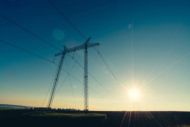 Aard minimaal landschap met silhouetten van hoogspanningsleidingen in veld tegen zonnige hemel