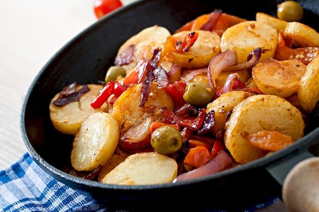 Aardappel in de schil met groenten in een pan
