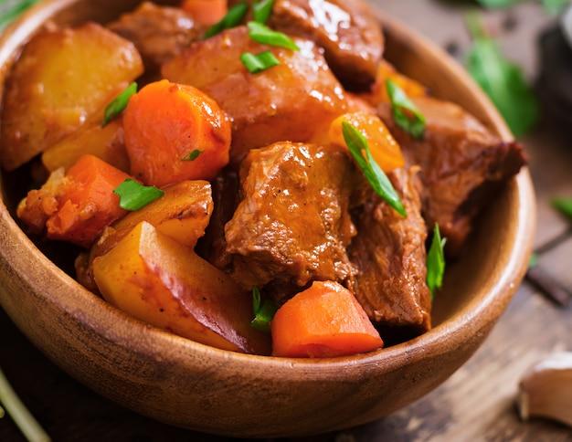 Aardappel in de schil met rundvlees bourguignon op de oude houten lijst in rustieke stijl