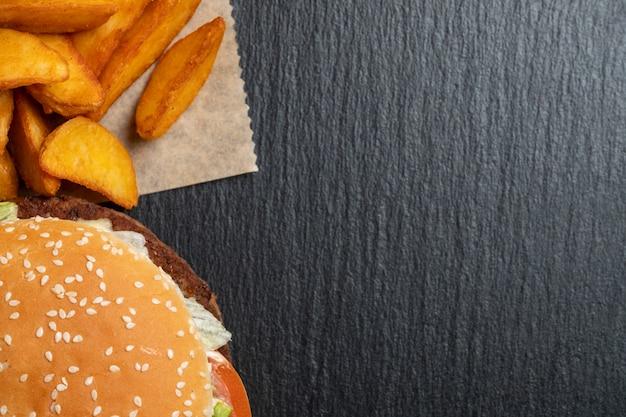 Aardappel in papier naast een hamburger op een leisteen, zwarte stenen gerechten. bovenaanzicht. kopieer ruimte.