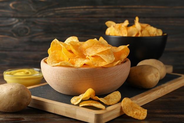 Aardappelchips. biersnacks, saus, aardappel op scherpe raad, op houten, ruimte voor tekst. detailopname