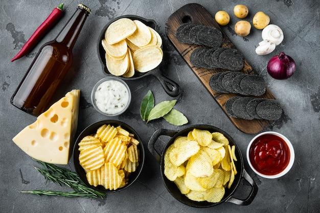 Aardappelchips. biersnacks, saus set met kaas en ui, met dipsauzen, op grijze stenen tafel, bovenaanzicht plat leggen