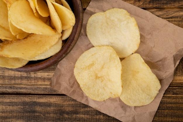 Aardappelchips in een kom en op een stuk papier over houten tafel.