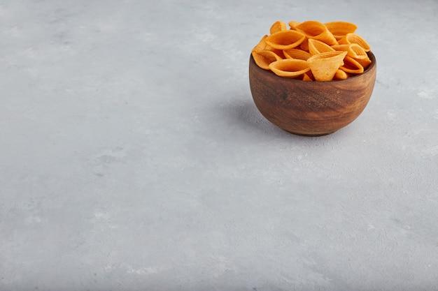 Aardappelchips in houten kom in de bovenhoek.