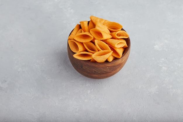 Aardappelchips in houten kom in het midden.