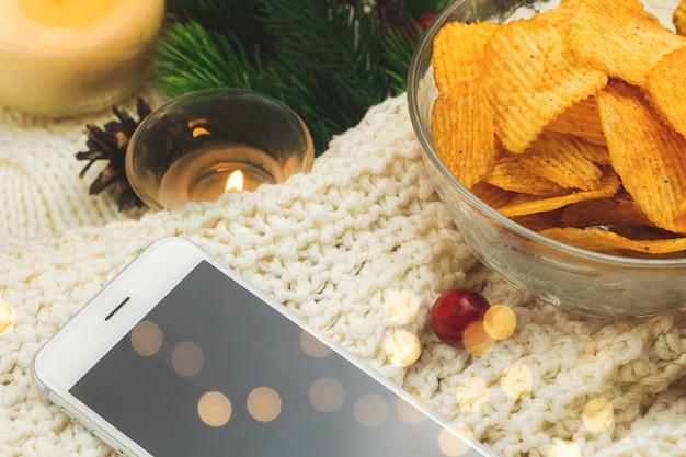 Aardappelchips in kom en smartphone, gezellige wintercompositie met slinger bokeh, wollen trui. hoge kwaliteit foto