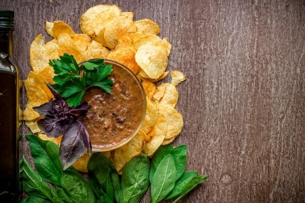 Aardappelchips met dipsaus op een houten tafel. ongezond voedsel op een houten achtergrond. bovenaanzicht. ruimte kopiëren. plat leggen. stilleven