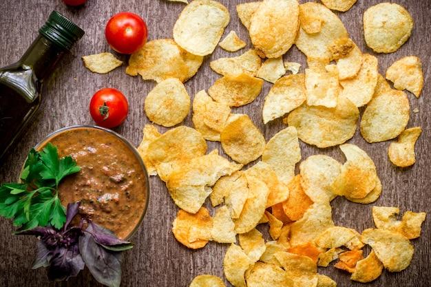 Aardappelchips met dipsaus op een houten tafel ongezond voedsel op een houten ondergrond