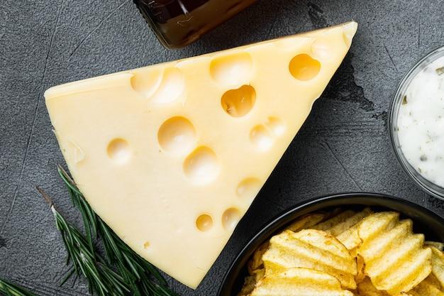Aardappelchips met kaas en ui, met dipsauzen, op grijze steen