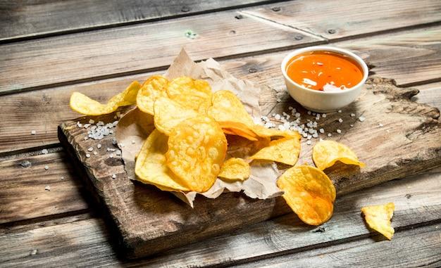 Aardappelchips op oud papier met tomatensaus op een rustieke tafel.