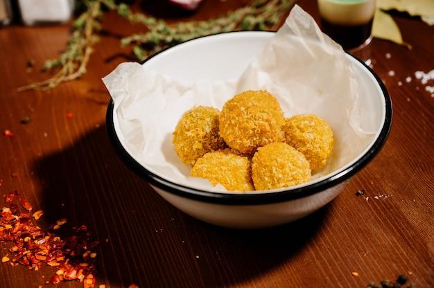 Aardappelcroquette-ballen met saus op een plaat.