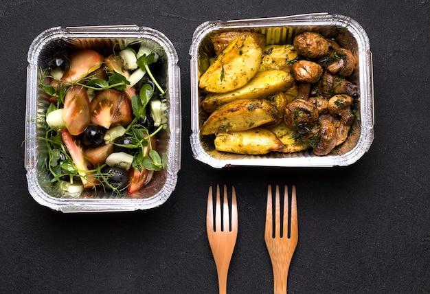 Aardappelen en champignons in een bakje naast salade en bestek. thuisbezorging concept