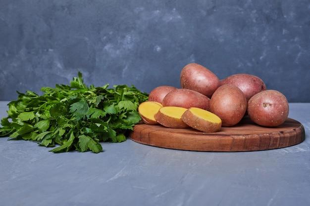 Aardappelen en kruiden op blauw