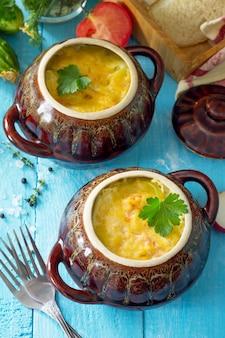 Aardappelen en rode vis met room en kaas bakken in kleipotten in de keuken houten achtergrond