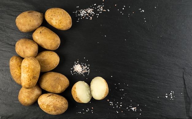 Aardappelen gekookt in hun huiden op donkere stenen achtergrond met plaats voor tekst. gekookte hele groenten bovenaanzicht