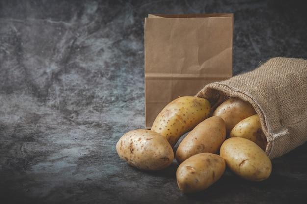 Aardappelen gieten uit zakken op grijze vloer