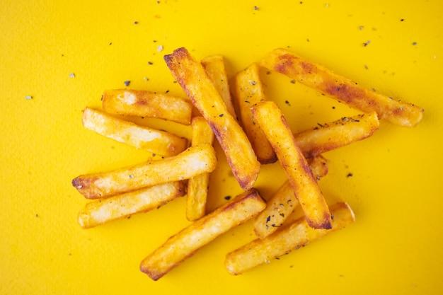 Aardappelen in de schil met aromatische kruiden op een gele achtergrond.